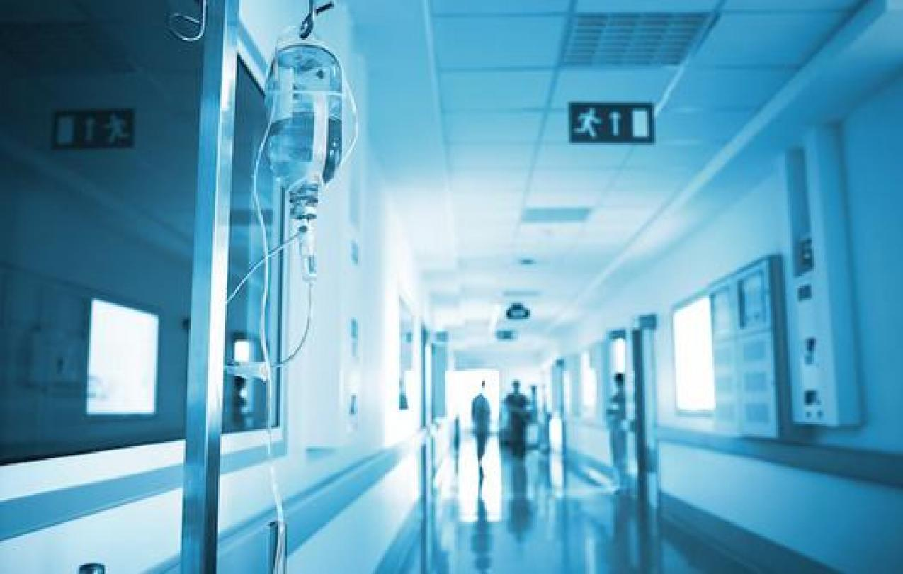 An IV drip is positioned in front of an out of focus hospital hallway.