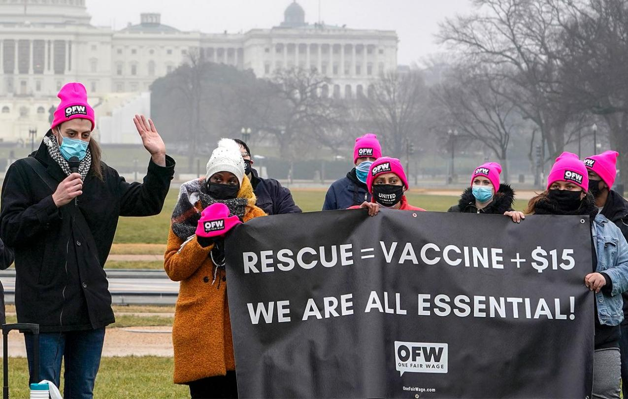 """Protestors holding banner that says """"RESCUE = VACCINE + $15"""", next line """"WE ARE ALL ESSENTIAL"""""""