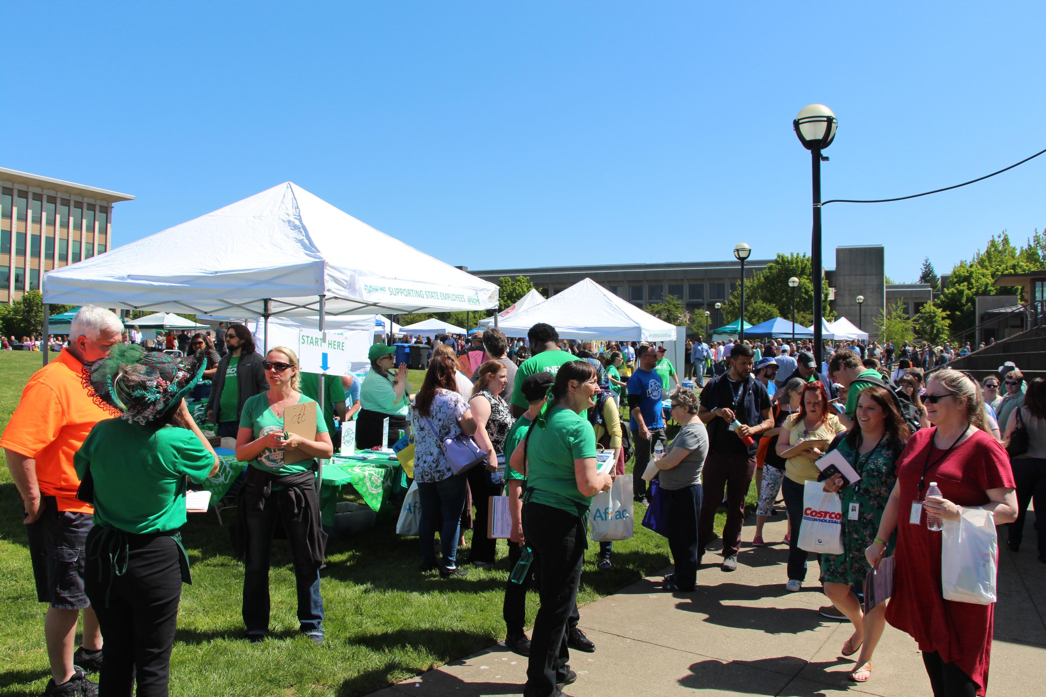 A crowd of public employees gather outside near tents.